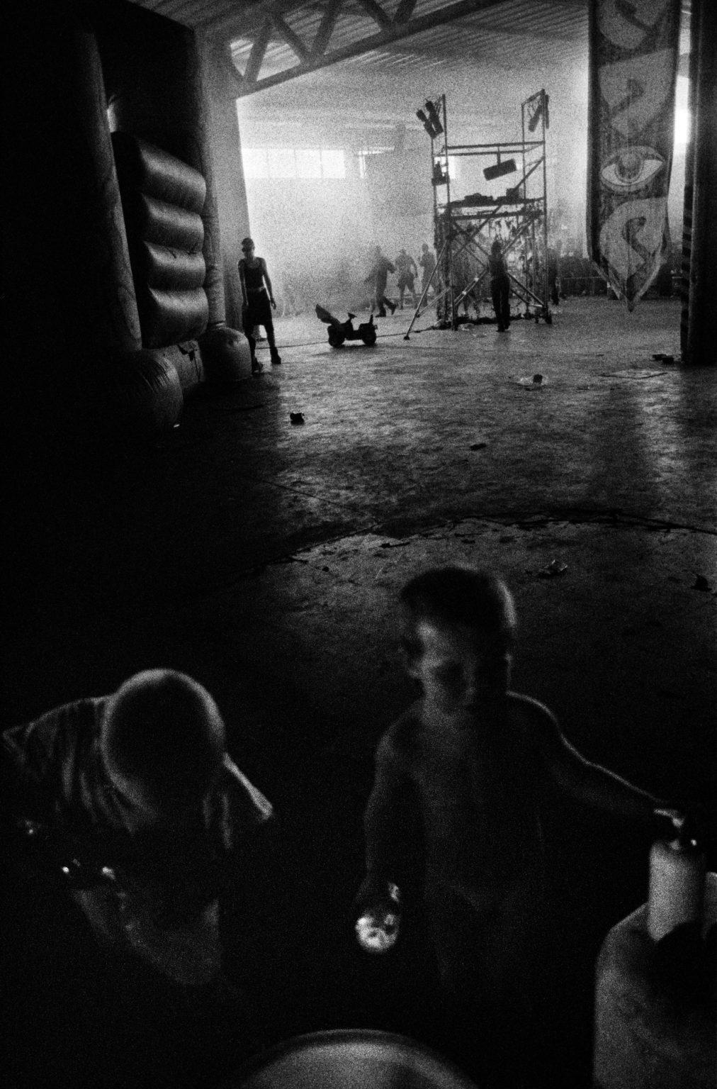 Bologna, 1997 - Summer rave party in an abandoned factory in Via Mazzini; in the outskirts of Bologna. This emilian city has always been on the foreground of the italian underground scene; since the punk invasion of the late 70s. Most of the deejays and travellers used to move around with their family. That's why in the first hours of the morning it was not unusual seeing little kids running around the party. >< Bologna, 1997 - Rave party estivo in una fabbrica abbandonata in Via Mazzini; nella periferia di Bologna. La città emiliana è sempre stata in primo piano nella scena underground italiana; dall'invasione punk della fine degli anni '70. La maggior parte dei deejay e dei viaggiatori si spostava con la famiglia. Ecco perché nelle prime ore del mattino non era insolito vedere bambini piccoli correre per la festa.