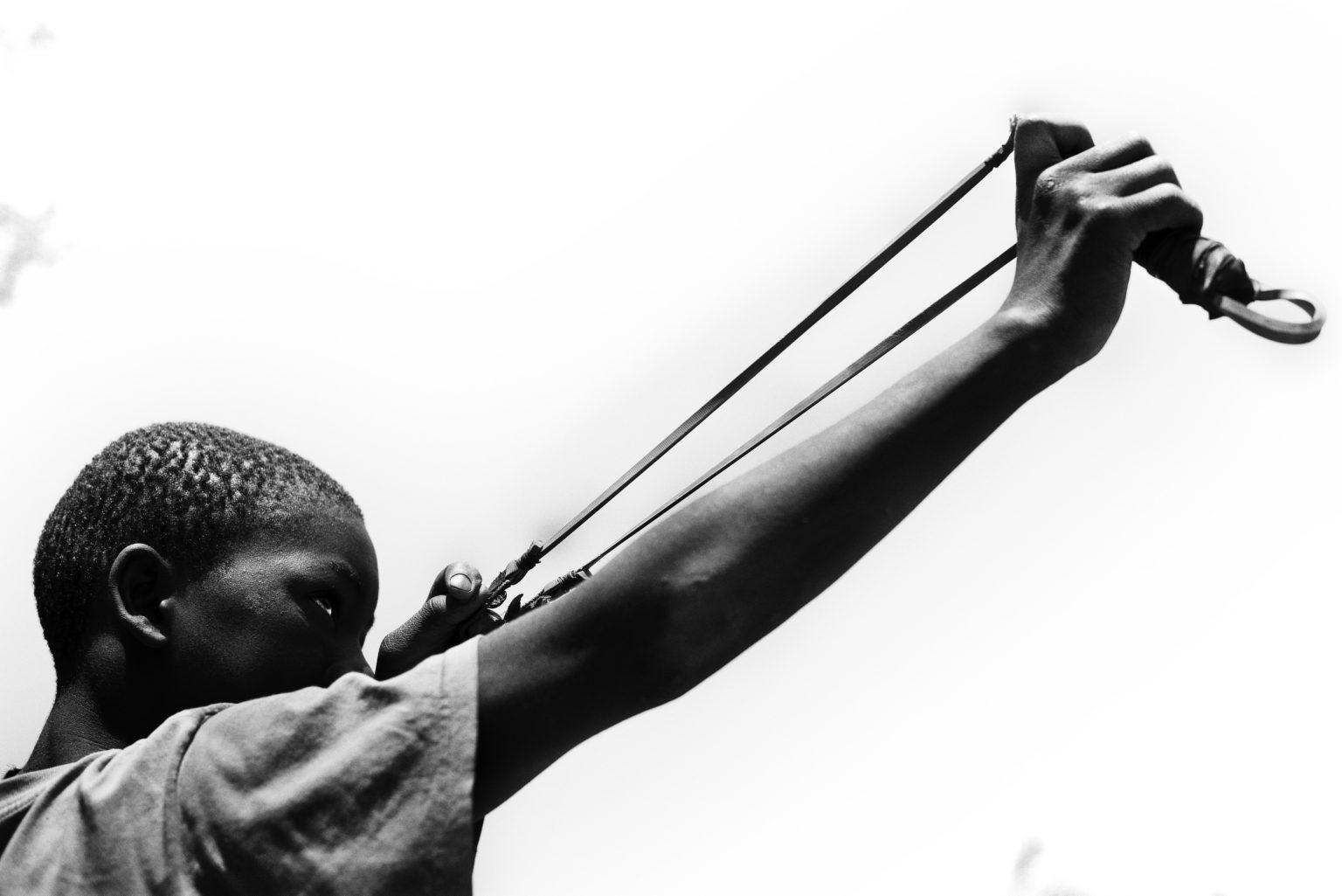 ragazzo si esercita con la fionda nel centro di Mthunzi