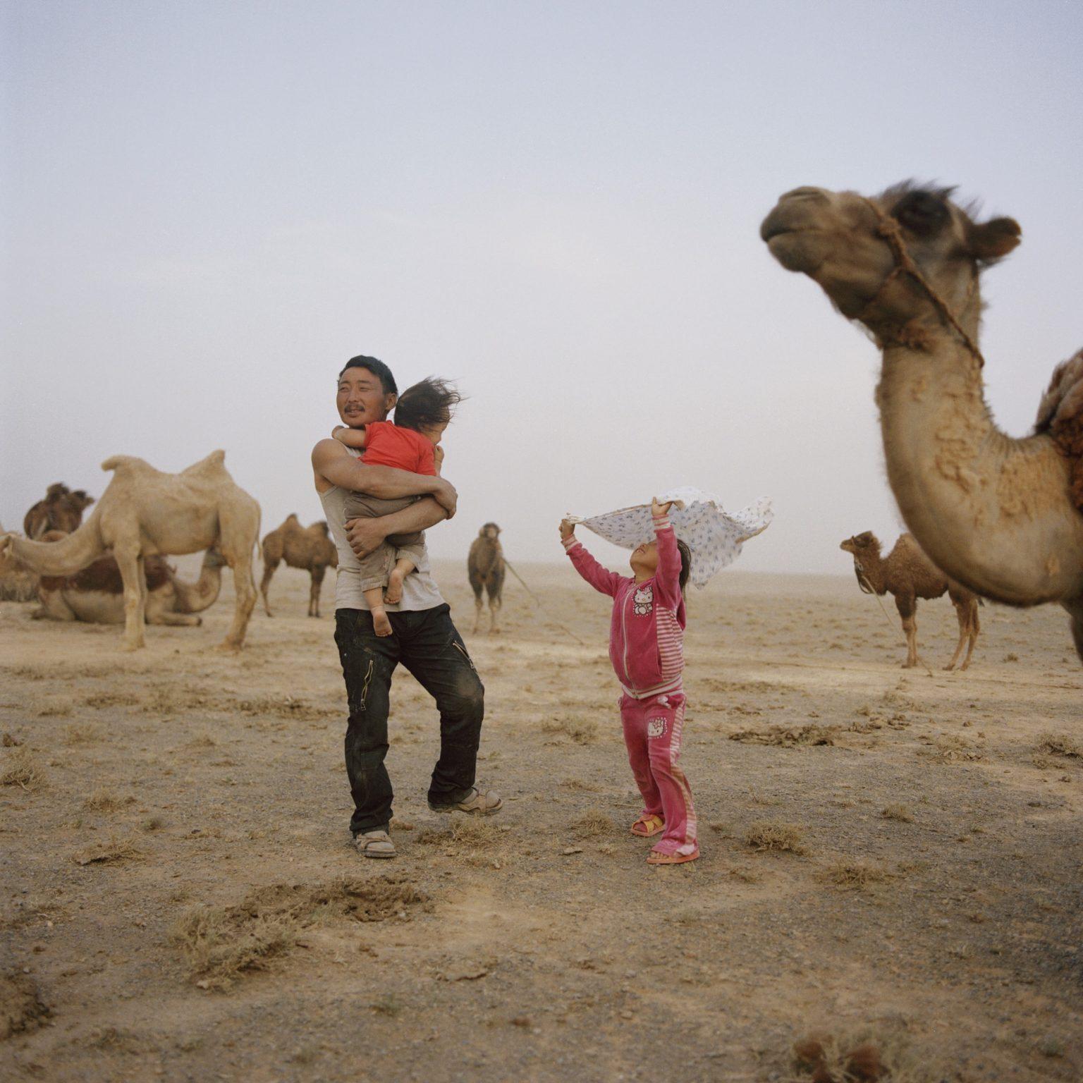 Tuvshinbayar Sugirsuren with his children during a sand storm. Omongovi, 2012