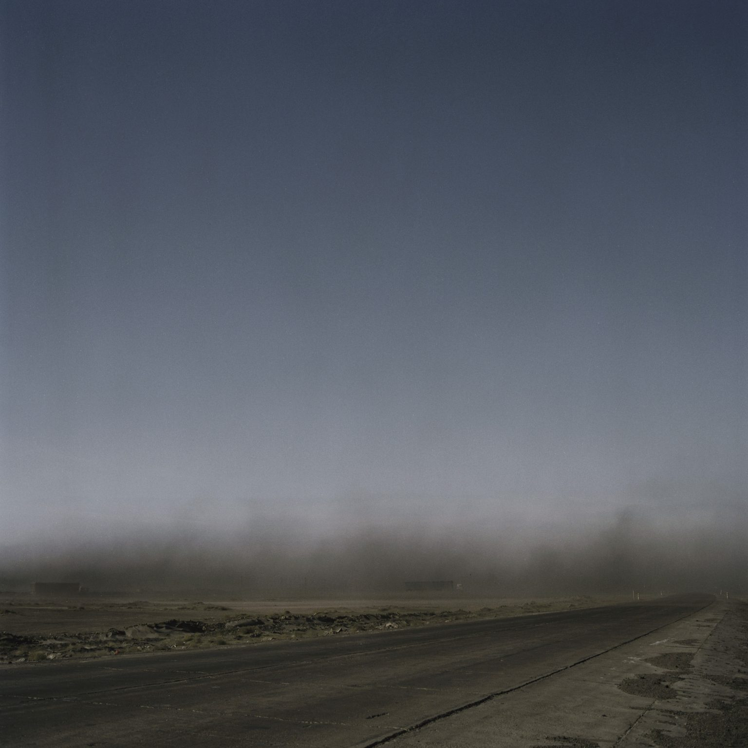 A cloud of coal dust in the road built by Energy Resource Mine to connect coal delivery from Mongolia to China. New roads interrupt wild animals and pasture's daily transit. Dust lifts as minetrucks pass through, and covers the surrounding vegetation, making it impossible for the cattle to feed themselves. White Mountains outpost, 2013