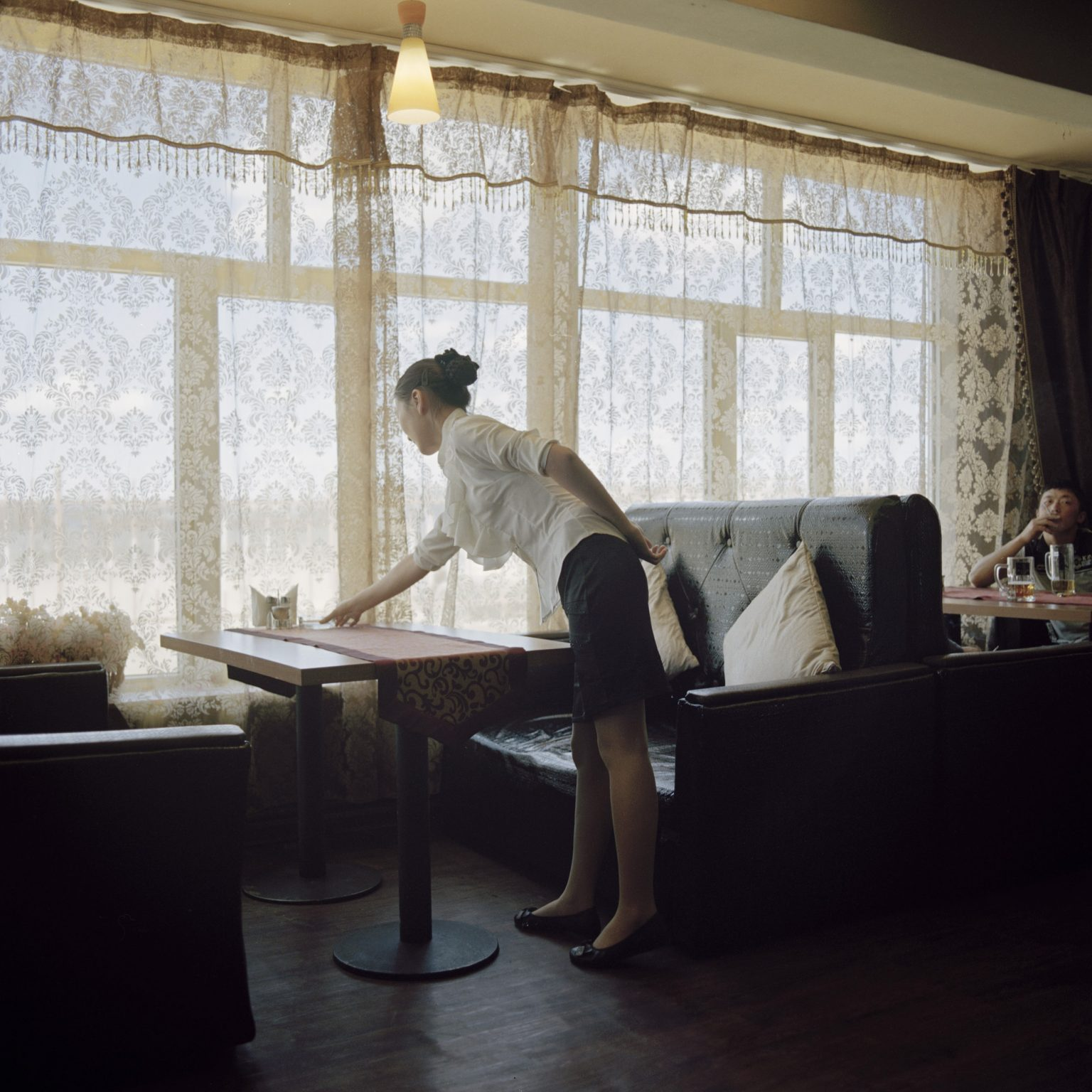 A Mongolian waitress working at the Broadway restaurant, the only one for foreigners in the sum. The westerner and Mongolian managers of the mining companies live in settlements built for them where the villagers are prohibited from accessing Tsogttsestiie sum, 2012