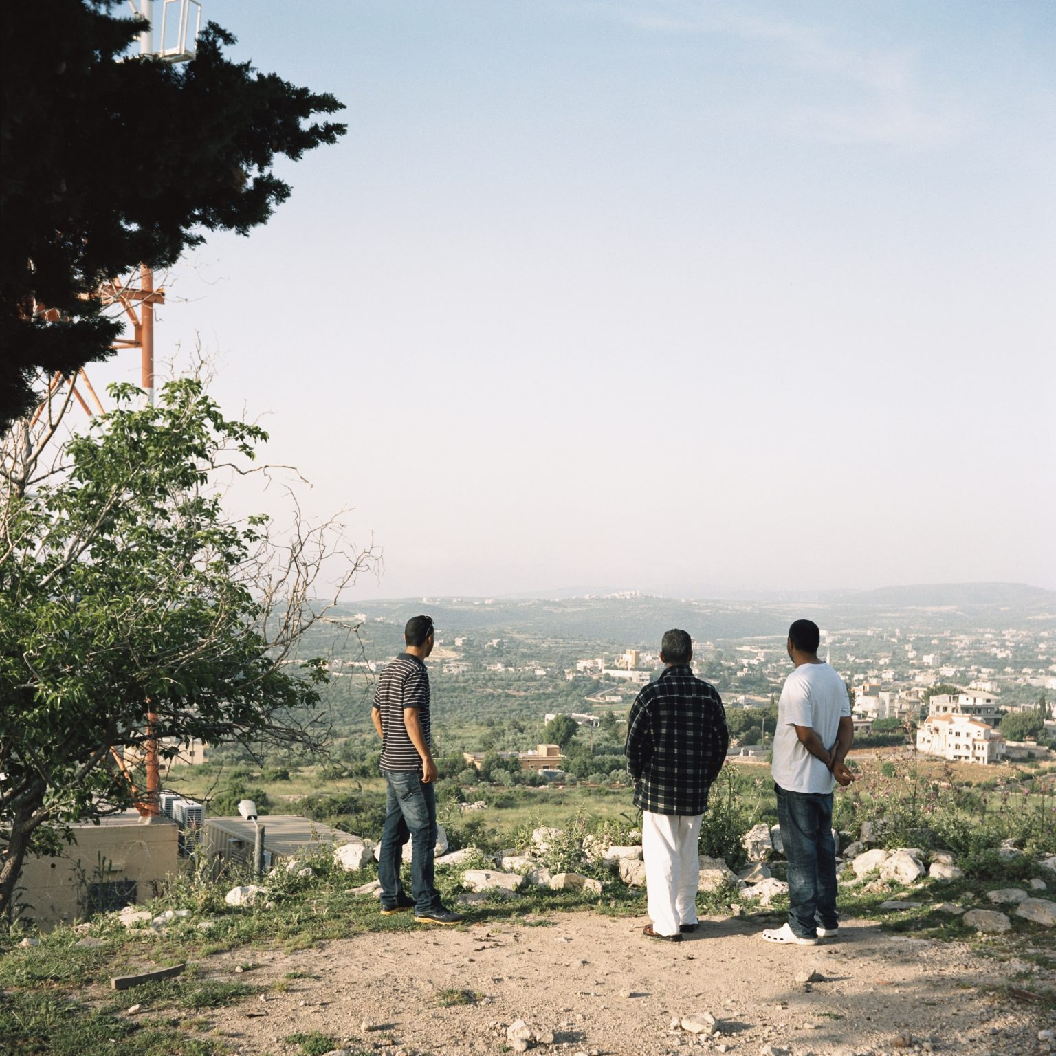 Arab al-Aramshe, Israel. Three residents of Arab al-Aramshe, a Bedouin village south of the Lebanese border, look the lebanese territory from a hill near the border area. Over the years, Aramshe residents have experienced attacks by Katyusha rockets launched from Southern Lebanon by the Hezbollah. During the 2006 Lebanon War, Fadiya Juma'a (age 60) and her daughters Samira (33) and Sultana (31) were killed by a Katyusha that fell in the garden of their home on August 5
