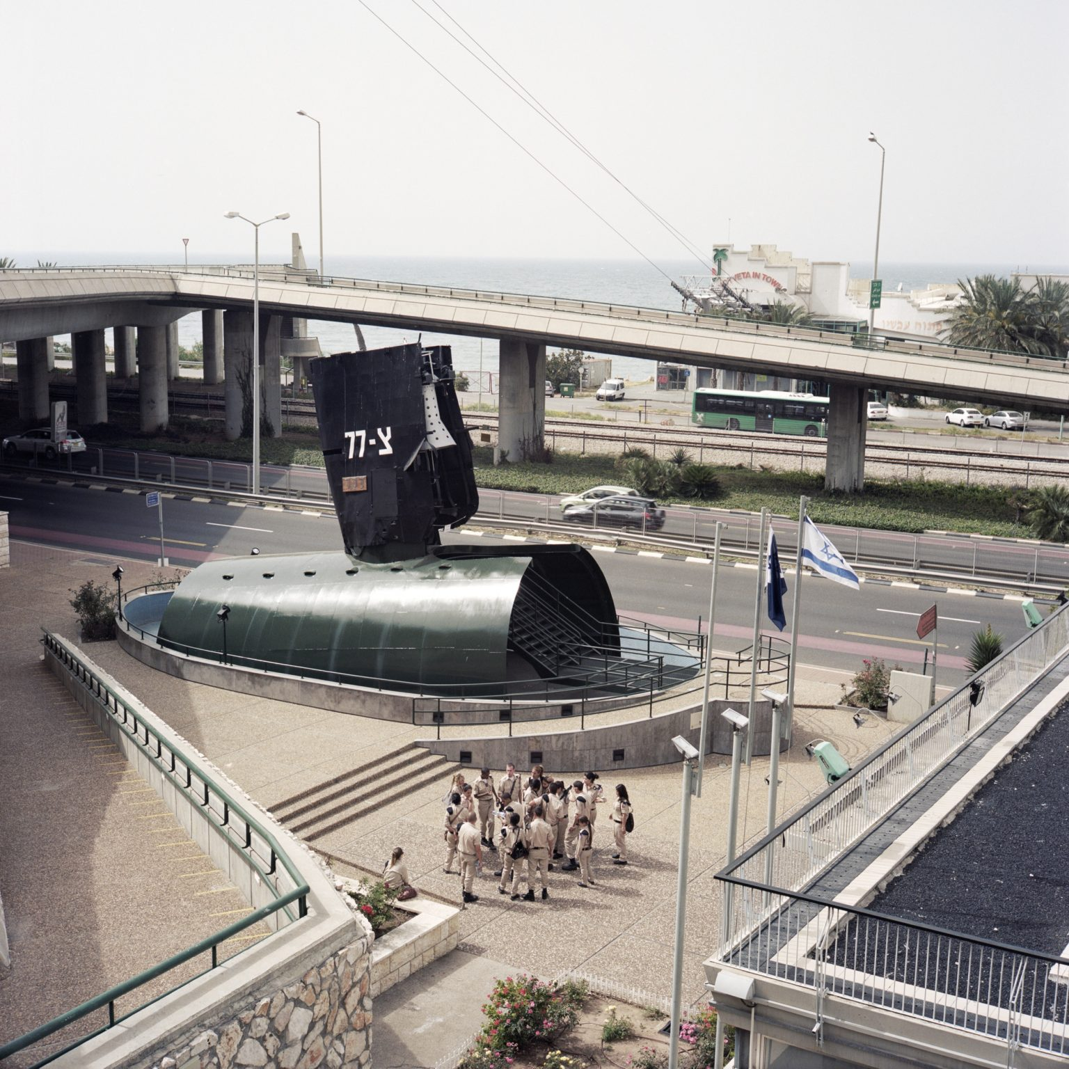 Haifa, Israel. A group of soldiers visiting the Navy museum, standing in front of the recovered conning tower of Dakar submarine, which sunk in 1968 between Cyprus and Crete.