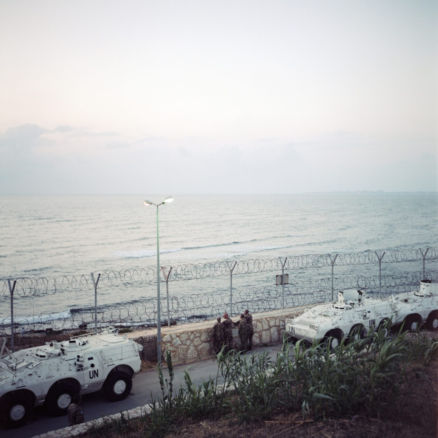 Al Mansouri, Lebanon. UNIFIL Italbatt compound, seat of Sector West Mobile Reserve. Soldiers look at the sea just outside the fence surrounding the base.