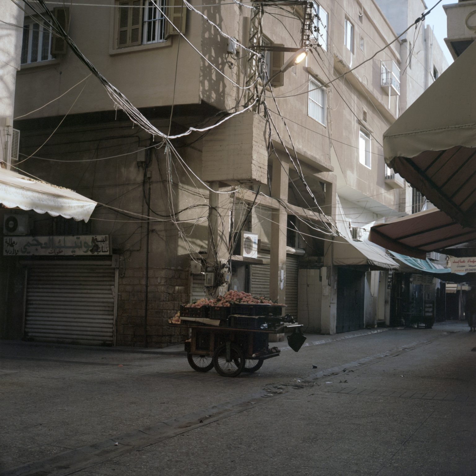Tyre, Lebanon. A peddling cart full of oranges is left in a street of the market after closure.